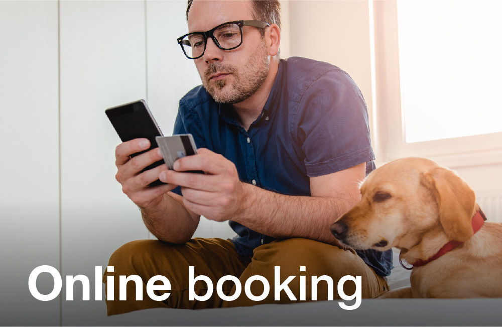 Tay Valley Vets Online Booking service image. Man with glasses looking at his phone with a brown dog on his left hand side